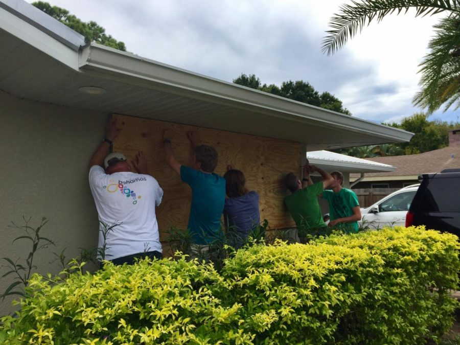 Carter Beckstein boards up windows with family and friends to prepare for Irma's arrival.