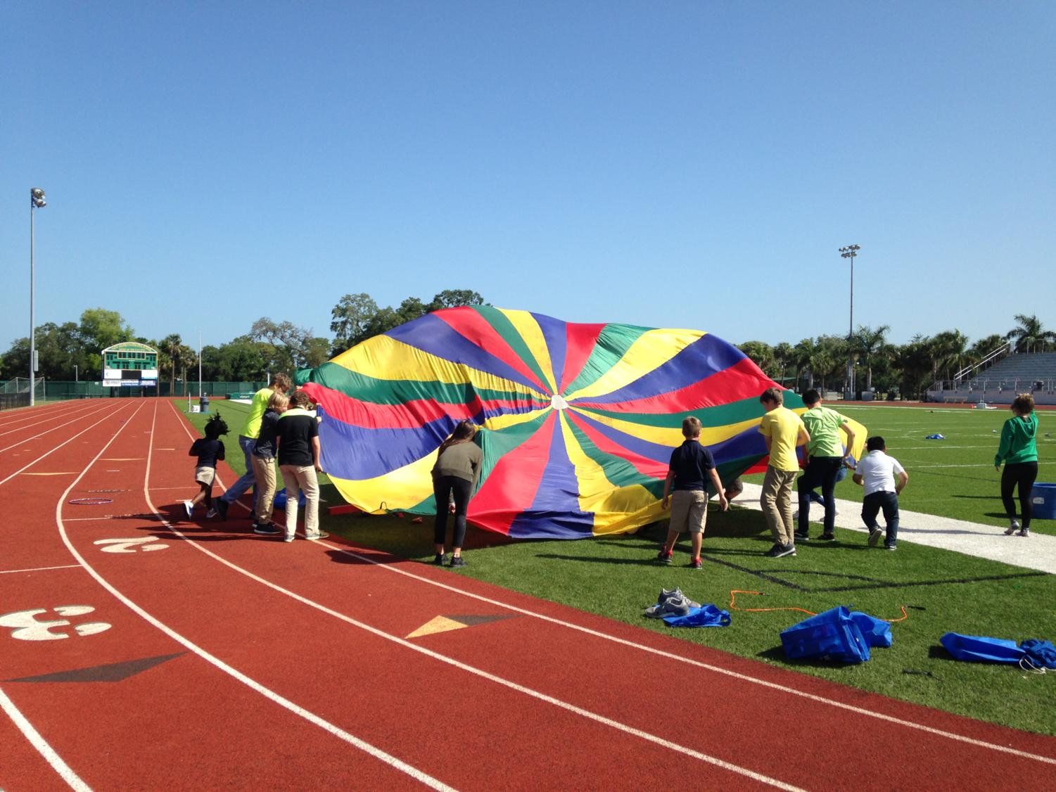 The kids let out some of their energy by playing with a parachute in the field.