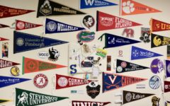 A collection of pennants from various universities is displayed on a wall of the college counseling office.
