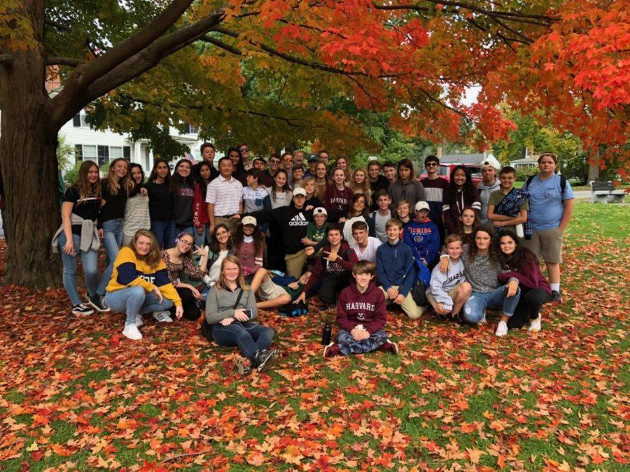 Eighth grade students gather among the leaves at Lexington Green for a group photo.