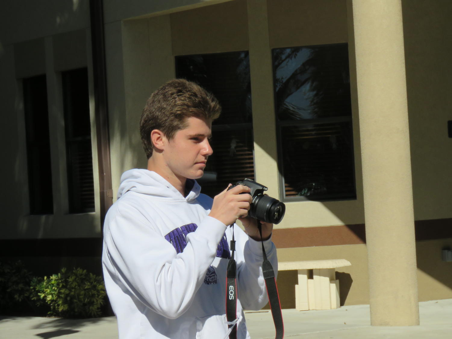 Senior Jarrett Millican taking photos in the Palm Courtyard.