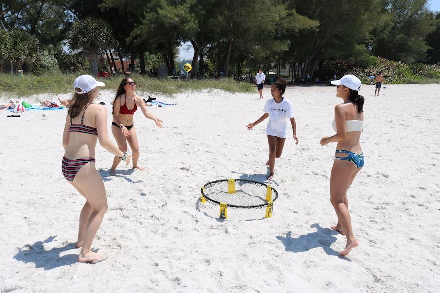 A group of junior girls play spikeball.