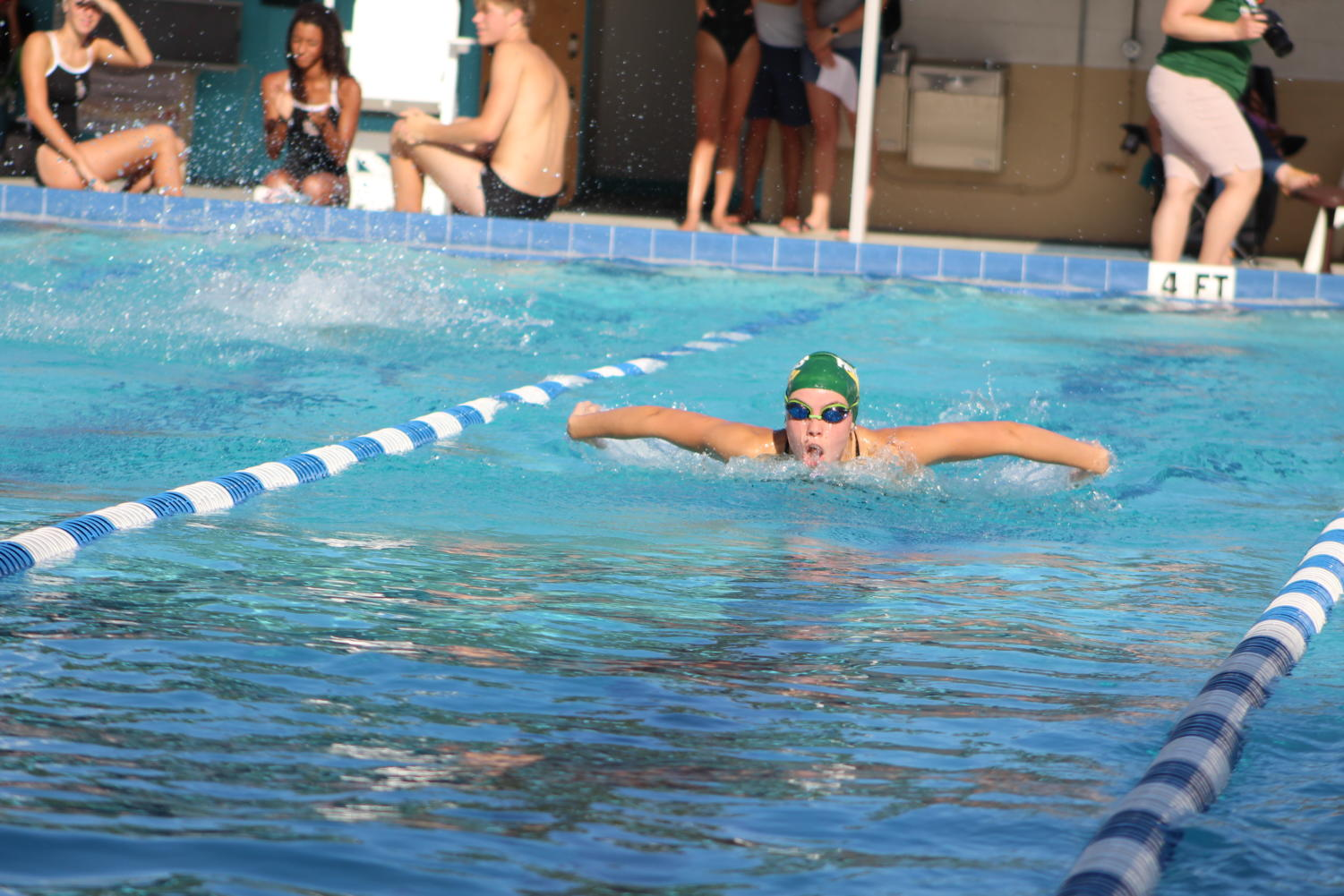 Senior swim team captain Anika Kennedy swims fast in her leg of the 200 medley relay: the 50 fly.