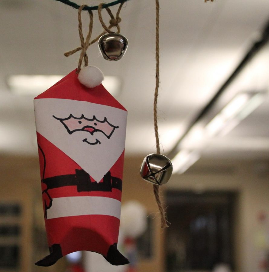 Mrs. DeZiel is getting festive by making a paper Santa and hanging it up on her door!